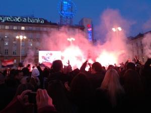 Jogadores se abraçando,  em campo; a fumaça vermelha começando, na Avenida Principal de Zagreb.